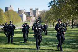 © Licensed to London News Pictures. 17/04/2021. Windsor, UK. Armed police on The Long Walk, next to Windsor Castle, in Windsor, Berkshire, ahead of the funeral of Prince Philip, The Duke of York. Prince Philip, the Consort of the longest reigning English monarch in history, Queen Elizabeth II, died on 9 April 2021, two months before his 100th birthday. . Photo credit: Ben Cawthra/LNP