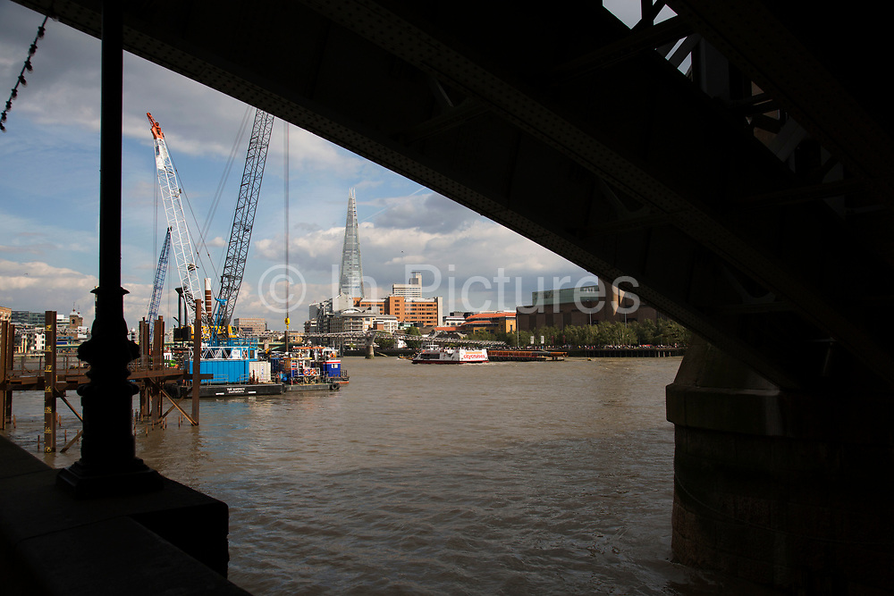 Construction work underway on the Thames Tideway Tunnel or Super Sewer on the River Thames near Blackfriars in London, England, United Kingdom. The Thames Tideway Tunnel is an under-construction civil engineering project 25km tunnel running mostly under the tidal section of the River Thames through central London, which will provide capture, storage and conveyance of almost all the combined raw sewage and rainwater discharges that currently overflow into the river.