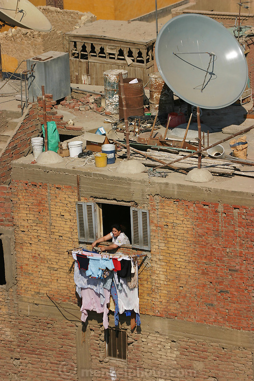 A woman hanging out laundry from her apartment window in Cairo, Egypt.