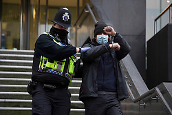 © Licensed to London News Pictures. 03/02/2021. London, UK. Police remove an activist. Bailiffs work to evict a group of eco-activists who are living in increasingly unstable tunnels beneath Euston Square Gardens in central London. The eviction of the HS2 Rebellion group from the square began one week ago and continues today. Photo credit: Marcin Nowak/LNP