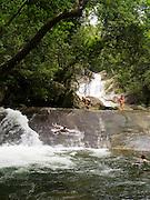 People enjoy sliding at Josephine Falls, within the Wooroonooran National Park, near Babinda, QLD, Australia.
