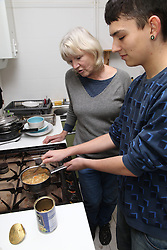 Teenage boy cooking meal with grandmother