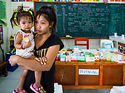 20 JANUARY 2018 - CAMALIG, ALBAY, PHILIPPINES: A girl with her daughter waits for a pharmacist in the clinic at the Barangay Salugan evacuee shelter in a school in Camalig. There are about 870 people living at the shelter. They won't be allowed to move back to their homes until officials determine that Mayon volcano is safe and not likely to erupt. More than 30,000 people have been evacuated from communities on the near the Mayon volcano in Albay province in the Philippines. Most of the evacuees are staying at school in communities outside of the evacuation zone.   PHOTO BY JACK KURTZ