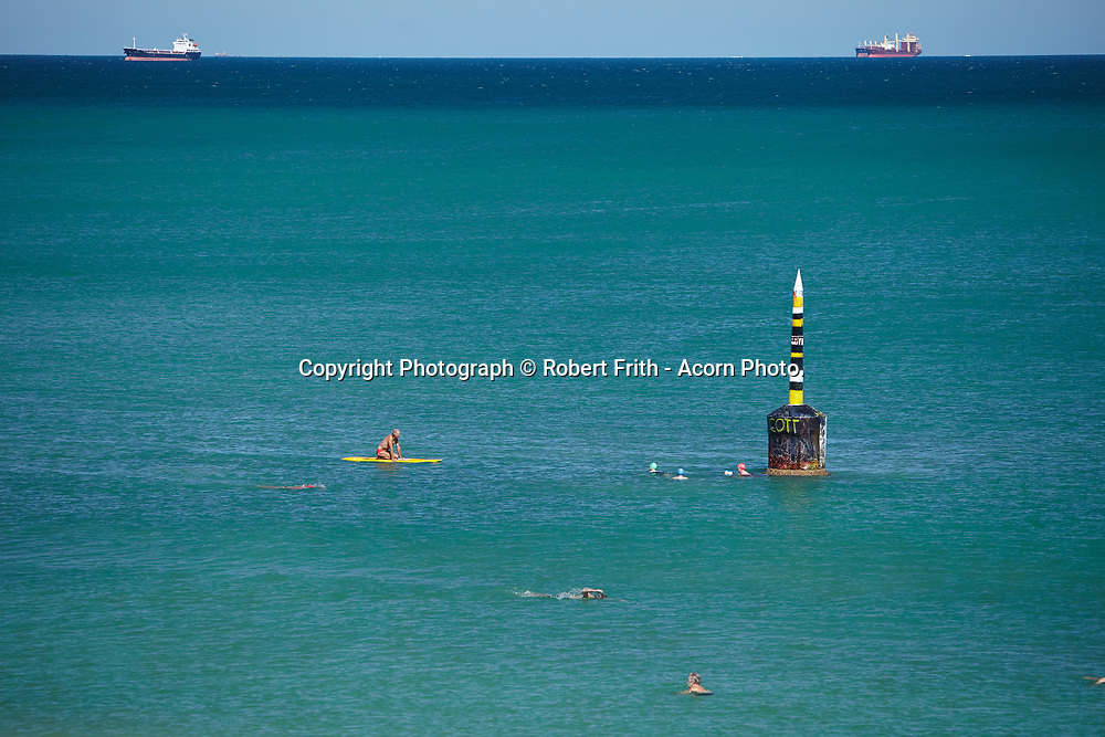 The pylon at Cottesloe Main Beach with freight ships in Gage Roads in the background
