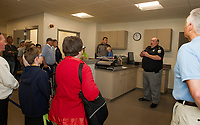 Captain Tim Dunleavy gives a tour of the Booking Room in the NH Dept of Safety Marine Patrol headquarters during their open house on Saturday morning.  (Karen Bobotas/for the Laconia Daily Sun)