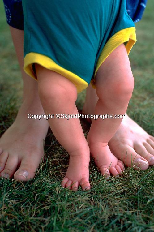 Mother age 30 and baby's bare feet enjoying fresh summer grass. Merriam Park St Paul Minnesota USA