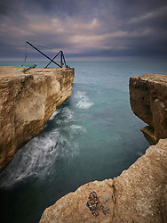 The Old Red Crane at Portland Bill in Dorset is a relic of the stone quarrying that happened all around the island coast. Photographed in evening light under a stormy sky.