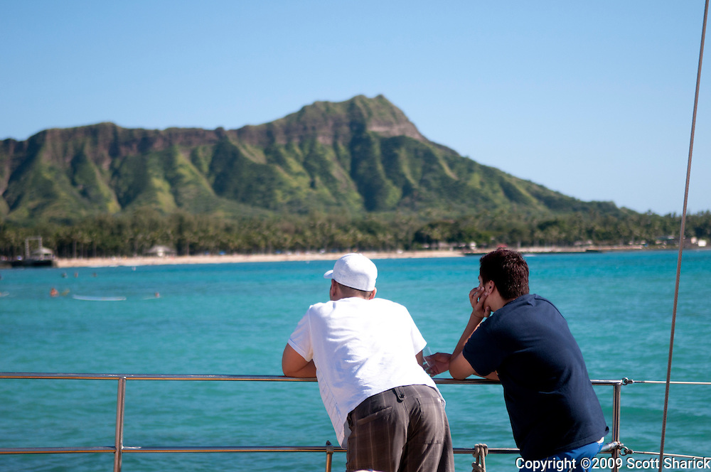 Two people on a boat looking at Diamond Head Crater.