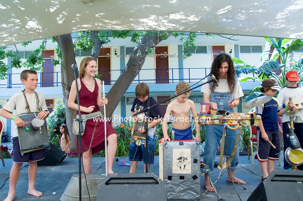 A music performance and demonstration by a musician who uses recycled trash and garbage to manufacture his musical instruments. A group of children trying out the home made instruments  to raise environmental awareness