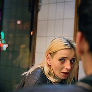 An illegal immigrant from Czeck, working as a prostitute, talks to her pimp in Amsterdam. She was beaten by two Yugoslav men but was too afraid to be deported to call the police...For illegal immigrants, simple needs such as food, sleep, money, work or dignity becomes hard to get.  .Photo taken by Justin Jin in November 2002.