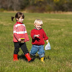A young brother (age 2) and sister (age 4) explore a field on the Common Pasture in Newburyport, MA. MR