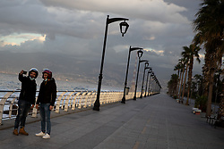© Licensed to London News Pictures. 15/01/2021. Beirut, Lebanon. People take a photo on the Corniche in Beirut, which is near empty on the second day of an 11 day curfew (from 14 Jan to 25 Jan) in an attempt to control a rapid increase in rates of COVID-19 Coronavirus in the country. Today, Lebanon registered two record-breaking statistics, with 6154 cases of Coronavirus, and 44 deaths in the past 24 hours. Photo credit : Tom Nicholson/LNP
