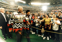 September 25, 1988 - Toronto, Ontario, Canada - Young at Heart: South African President NELSON MANDELA and his wife GRACA MACHEL, dressed in fleece jackets given to him by aboriginal leaders; smile with delight as they enter a SkyDome filed to the rafters with more than 40,000 schoolchildren. (Credit Image: Ken Faught/Toronto Star/ZUMAPRESS.com)