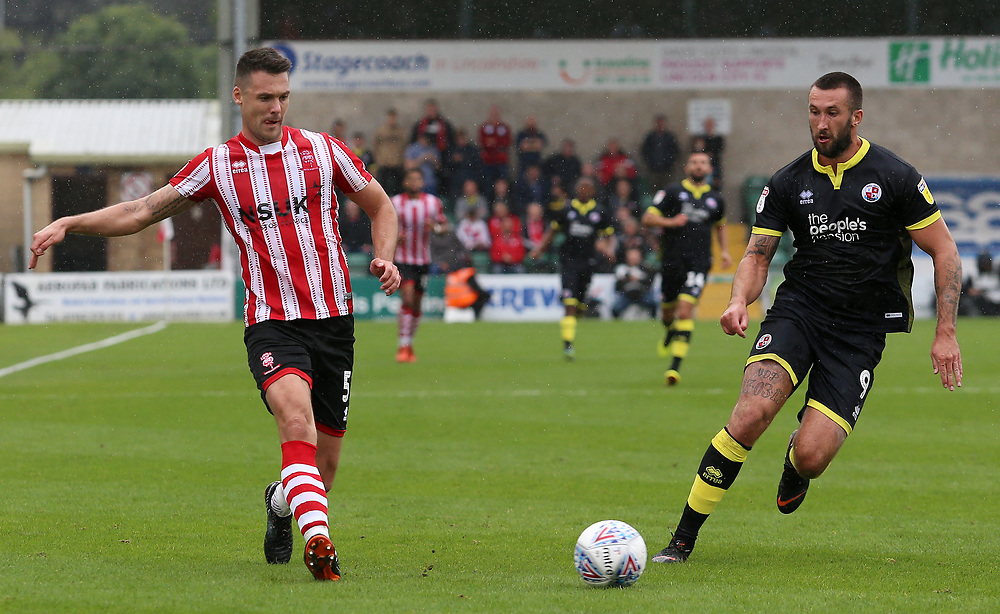 Lincoln City's Jason Shackell plays the ball past Crawley Town's Ollie Palmer<br /> <br /> Photographer David Shipman/CameraSport<br /> <br /> The EFL Sky Bet League Two - Lincoln City v Crawley Town - Saturday September 8th 2018 - Sincil Bank - Lincoln<br /> <br /> World Copyright © 2018 CameraSport. All rights reserved. 43 Linden Ave. Countesthorpe. Leicester. England. LE8 5PG - Tel: +44 (0) 116 277 4147 - admin@camerasport.com - www.camerasport.com
