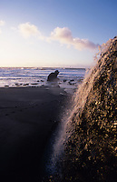 Water falls onto the beach at Sea Ranch, California.