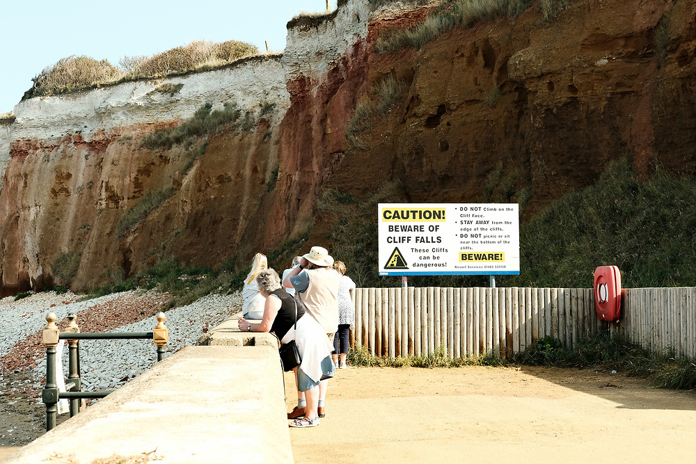 People stand on the promenade looking at the Jurassic cliffs in Hunstanton next to a sign warning of the danger of falling rocks.<br /> On the last hot day of the Summer in Hunstanton Norfolk, the first summer in the UK during the COVID-19 pandemic.<br /> <br /> Photo by Jonathan J Fussell, COPYRIGHT 2020