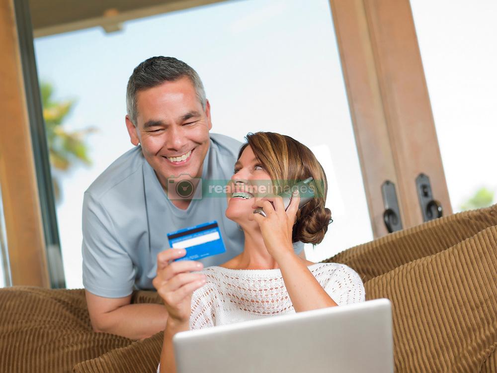 Couple shopping on telephone (Credit Image: © Image Source/Dan Bannister/Image Source/ZUMAPRESS.com)