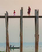 Monk and boy meet on the U-Bein Bridge in the morning light. U-Bein Bridge crosses the Taungthaman Lake near Amarapura in Myanmar. The 1.2-kilometre bridge was built around 1850 and is believed to be the oldest and longest teakwood bridge in the world.
