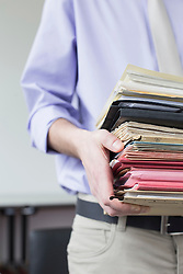 Businessman holding stack of files in office, close up