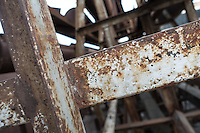 A rusty steel metal brace forms a cross, lying in a junkyard. White paint covers the metal of the brace, covered with rusty patches.