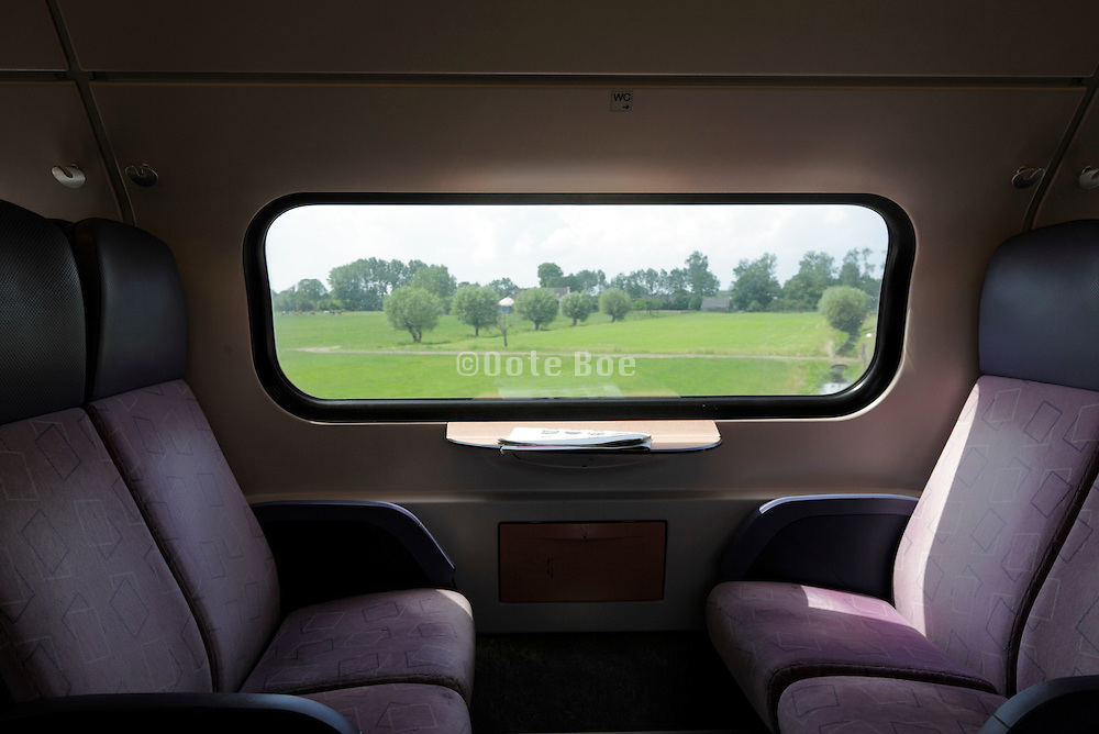 window view from train with empty seats Holland