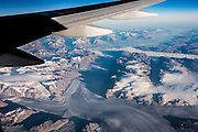 Seen through a jet window, a vast ice sheet stretches across Greenland, the world's largest island. This ice cap (Sermersuaq in Greenlandic) contains 10 percent of the world's fresh water, plus atmospheric particles which scientists can use to gain an insight into the climate of both Greenland and the Earth going back some 250,000 years. Scientists report accelerated melting since the new millennium, with a net loss of ice mass. If the entire ice sheet melted, the world's oceans would rise by 6-7 meters (20-23 feet). Greenland's huge ice sheet is only second in size to the Antarctic Ice Sheet. Greenland lies between the Arctic and Atlantic Oceans, east of the Canadian Arctic Archipelago. While it is physiographically part of the North American continent, for more than a thousand years Greenland has been politically and culturally associated with Europe (the colonial powers of Norway and Denmark, plus the nearby island of Iceland). In 2008, the people of Greenland passed a referendum making it an autonomous country within the Danish Realm. With a population of about 56,480 in 2013, it is the least densely populated country in the world. (The continent of Australia is larger but isn't considered an island.)