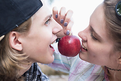 Close-up of young couple biting on a red apple, Bavaria, Germany