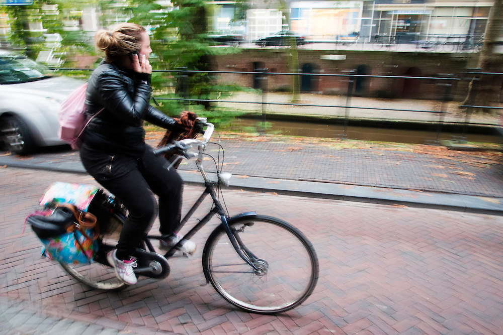 In Utrecht fietst een meisje al bellend over de Oudegracht.<br /> <br /> In Utrecht a girl cycles at the Oudegracht while phoning.