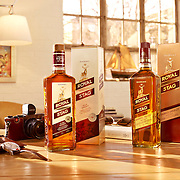 Royal Stag whisky products on a table with a selection of gadgets Ray Massey is an established, award winning, UK professional  photographer, shooting creative advertising and editorial images from his stunning studio in a converted church in Camden Town, London NW1. Ray Massey specialises in drinks and liquids, still life and hands, product, gymnastics, special effects (sfx) and location photography. He is particularly known for dynamic high speed action shots of pours, bubbles, splashes and explosions in beers, champagnes, sodas, cocktails and beverages of all descriptions, as well as perfumes, paint, ink, water – even ice! Ray Massey works throughout the world with advertising agencies, designers, design groups, PR companies and directly with clients. He regularly manages the entire creative process, including post-production composition, manipulation and retouching, working with his team of retouchers to produce final images ready for publication.