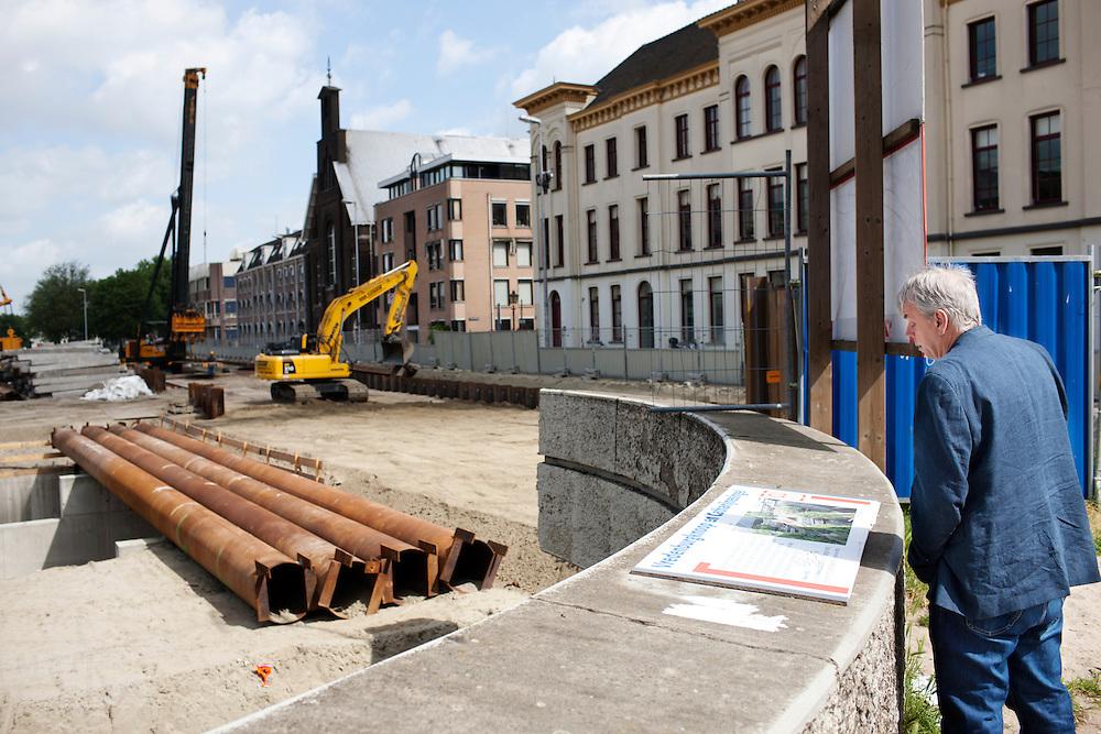 Een man leest een informatiebord over de werkzaamheden aan de Catherijnesingel. De voormalige weg wordt weer water.<br /> <br /> A man is reading an information sign about the construction that is going on.