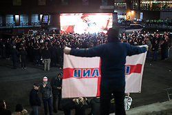 """© Licensed to London News Pictures . 03/11/2017 . Manchester , UK . A man with an England flag stands up as TOMMY ROBINSON (real name Stephen Yaxley-Lennon ) speaks to supporters at the launch of the former EDL leader's book """" Mohammed's Koran """" at Castlefield Bowl . Originally planned as a ticket-only event at Bowlers Exhibition Centre , the launch was moved at short notice to a public location in the city . Photo credit : Joel Goodman/LNP"""
