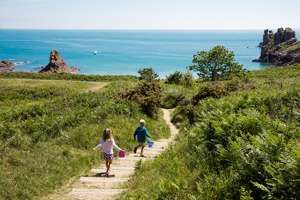Children running with buckets down the steps and pathway to Beauport beach with its calm blue sea in the sunshine on a Spring day in Jersey, CI