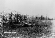 World War I 1914-1918: German sniper wearing a pickelhelm, lying on the ground behind barbed wire entanglements, rifle at the ready.