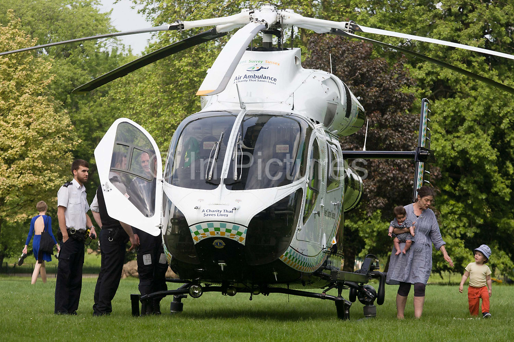 MD902 Explorer helicopter from the Kent, Surrey & Sussex Air Ambulance Trust on the ground in Ruskin Park after emergency flight to Kings College Hospital in south London. A mother takes her small children up close to the aircraft while on the other side, one of the pilots shows two Met police officers the features inside the cockpit before the aircraft lifts off again for another emergency case. The Air Ambulance (KSSAAT) fly state of the art Helicopter Emergency Medical Service (HEMS) aircraft operating 365 days a year, out of their base at Marden in Kent and Redhill in Surrey. They're capable of delivering our crews anywhere in our region in under 20 minutes flying time, attending over 20,000 missions