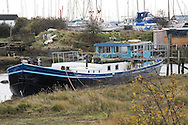 A wisp of smoke escapes from the stovepipe of a houseboat-barge moored in Tollesbury Saltmarsh