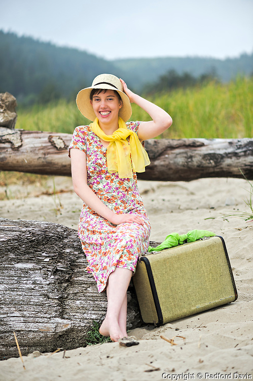 Woman on Cannon Beach with suitcase. Vintage look.
