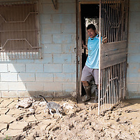 A man emerges from his flooded house in La Planeta to survey drying mud around him.<br /> <br /> Hurricanes Eta and Iota hit hard on the north coast of Honduras, leaving some areas flooded for three weeks, destroying people's furniture, belongings, vehicles and houses as well as standing crops.