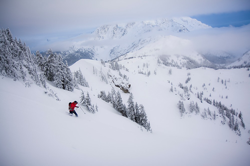 Telemark skier Abram Dickerson links together turns through deep powder in the backcountry, Mount Baker-Snoqualmie National Forest, Washington. Mount Baker is visible in the background.