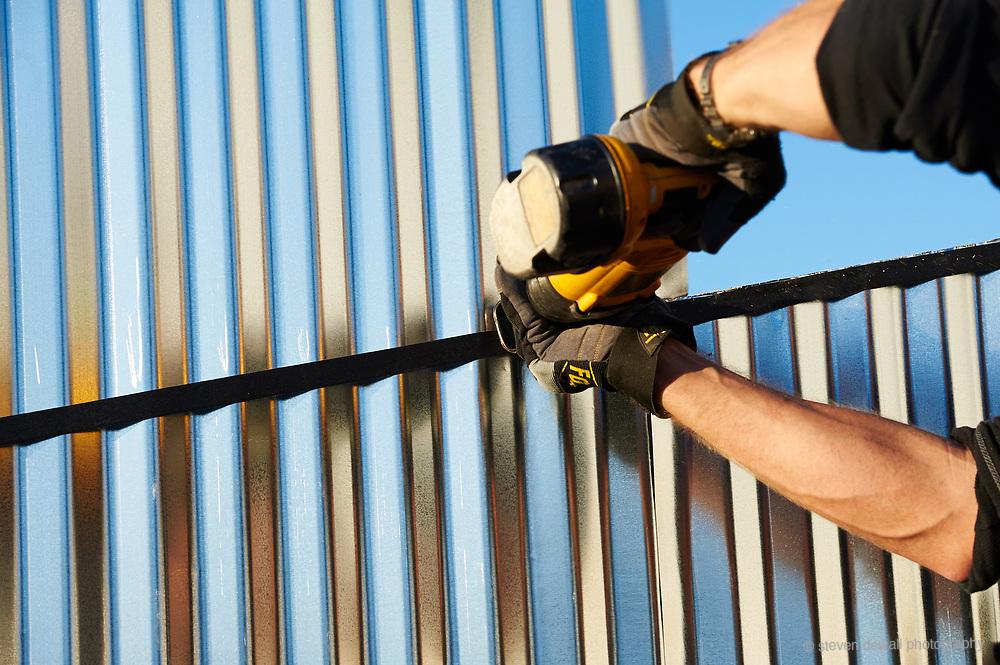 Carpenter cutting corrugated metal siding