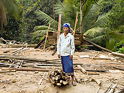 """A Laoseng ethnic minority woman returns to the old village to collect firewood after her village of Ban Watai has been temporarily relocated away from the Nam Ou river, during the construction of the Nam Ou Cascade Hydropower Project Dam 6, Phongsaly Province, Lao PDR. The Nam Ou river connects small riverside villages and provides the rural population with food for fishing. It is a place where children play and families bathe, where men fish and women wash their clothes. But this river and others like it, that are the lifeline of rural communities and local economies are being blocked, diverted and decimated by dams. The Lao government hopes to transform the country into """"the battery of Southeast Asia"""" by exporting the power to Thailand and Vietnam."""
