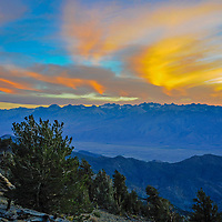 The sun sets over the Palisade region of the eastern Sierra Nevada, above the Owens Valley, California. In the foreground are the White Mountains and Ancient Bristlecone Pine Forest.