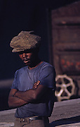 Black South African dock work stands in blue t-shirt and hat by railroad car in Capetown docks, South Africa