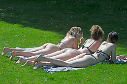 © Licensed to London News Pictures 18/07/2021. Greenwich, UK. Three friends sunbathing in Greenwich Park, London as the hot heatwave weather continues today with temperatures expected to hit 30C. Photo credit:Grant Falvey/LNP