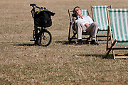 A man with a Brompton Bicycle sitting in a deckchair in St Jamess Park in London, England during sunny weather in the ongoing summer heatwave on August 07, 2018.