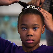 """Aliyah Randle sits on a chair in the kitchen while Lorraine Agnew fixes her hair for the adoption hearing, March 28, 2018. """"Never again will you have to worry about them coming to take you away,"""" Lorraine says. Aliyah leans her head back against her stomach. """"Never again,"""" Aliyah repeats."""