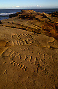 Visiting and local peoples' names carved into soft rock in the north-east coastal town of Cullcoates, Tyneside, England. The Christian names of Paul, Chris and John plus the Beatles and the year of 1981 have been gouged into the soft geology, read clearly in backlit sunshine. In the distance are the smooth waters of the North Sea