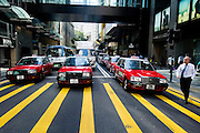 HONG KONG - APRIL 13: A white-collar employee crosses the street in front of taxis in Central business district, on April 13, in Hong Kong. (Photo by Lucas Schifres/Pictobank)