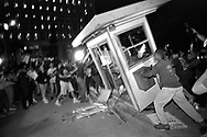 Rioters overturn and burn a parking kiosk near Parker Center, LAPD headquarters, in downtown Los Angeles.