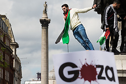 London, UK. 22nd May, 2021. A man stands on the plinth of a statue as tens of thousands of people approach Trafalgar Square during the National Demonstration for Palestine. It was organised by pro-Palestinian solidarity groups in protest against Israel's recent attacks on Gaza, its incursions at the Al-Aqsa mosque and its attempts to forcibly displace Palestinian families from the Sheikh Jarrah neighbourhood of East Jerusalem.