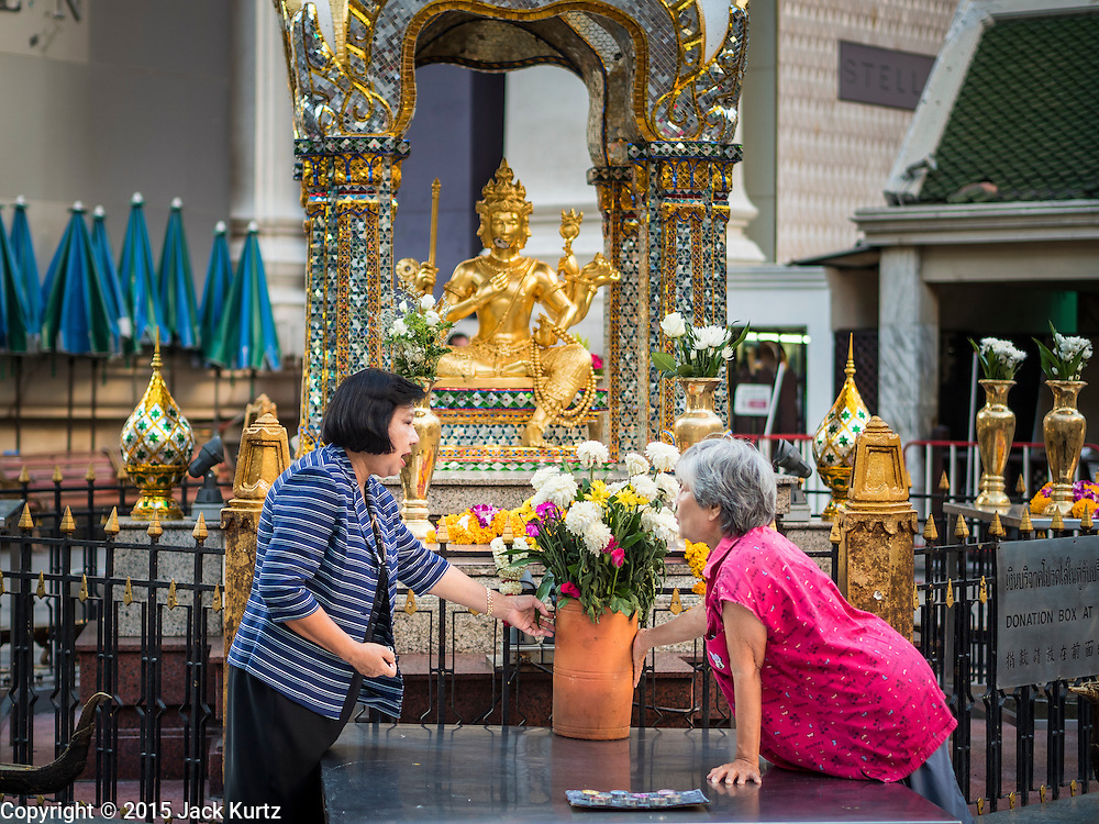 19 AUGUST 2015 - BANGKOK, THAILAND:  Women get Erawan Shrine ready to open. Erawan Shrine in Bangkok reopened Wednesday morning after more than 20 people were killed and more than 100 injured in a bombing at the shrine Monday, August 17, 2015. The shrine is a popular tourist attraction in the center of Bangkok's high end shopping district and is an important religious site for Thais. No one has claimed responsibility for the bombing.       PHOTO BY JACK KURTZ